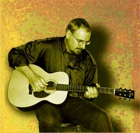 Picture of Todd playing a Santa Cruz acoustic guitar.